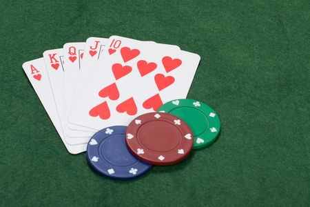 Playing a winning game of poker with playing cards overturned displaying a royal straight flush in hearts on green baize with casino chips
