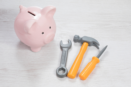 Household tools with a piggy bank conceptual of the costs or funding for home renovations, DIY or maintenance and repair viewed from a high angle on white wood Stock Photo