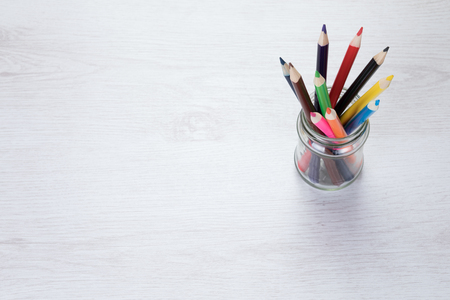 Glass jar filled with colored pencil crayons viewed from above in an education or art concept with copy space alongside