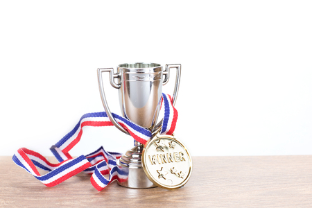 Silver trophy with gold medallion on a ribbon entwined through the handles conceptual of a win in a competition or championship with copy space