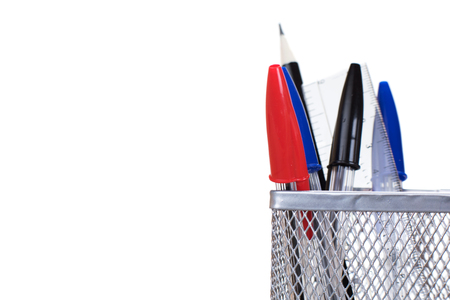 Wire mesh desk tidy with three red, blue and black ballpoint pens, a pencil and ruler in a concept of business or education with copy space alongside