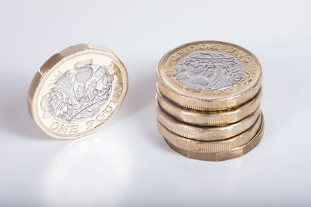 alongside: Detail of the new British pound coin with a high angle view on a stack and a single coin standing on edge alongside showing the engraving Stock Photo