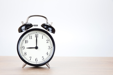 puntualidad: Anticuado reloj de alarma negro redondo con dos campanas de pie sobre una mesa de madera frente a la cámara con espacio de copia lateral