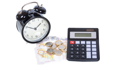 Accounting and business financial concept with an alarm clock and calculator alongside a heap of pound sterling coins and bills on white Фото со стока