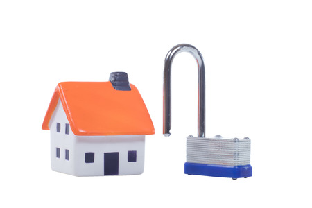 Small model house alongside a strong steel padlock with the shank open side by side on white with copy space