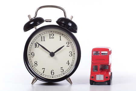 Big classic alarm clock with black hands and white face and small red London double-decker bus toy, viewed close-up in front against white background