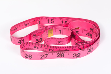 Pink measure tape marked in inches, on white surface