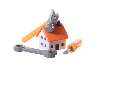 Model house in a home improvements and DIY concept with a tool kit arranged as a still life isolated on white with copy space