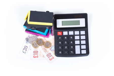 Cost of printer cartridges concept with stack of color ink consumables and simple calculator over GBP cash money, viewed from above and isolated on white background 版權商用圖片