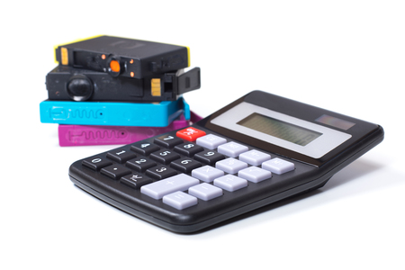 Color printer ink cartridges with simple calculator, close-up detail view from the side, symbolising consumables expenses concept, isolated on white background