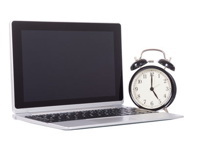 Alarm clock with open blank laptop computer conceptual of business time management and deadlines isolated on white