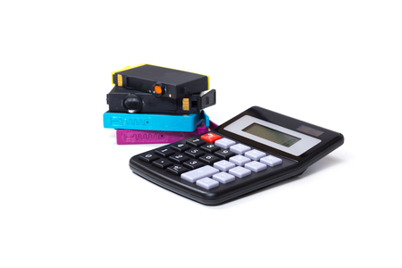 Color printer ink cartridges with simple calculator, viewed from the side, symbolising consumables expenses concept, isolated on white background 版權商用圖片