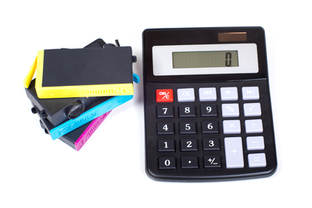 Stack of jet-ink printer cartridges and simple calculator viewed from above isolated on white background. Concept symbolising cost of consumables expenses