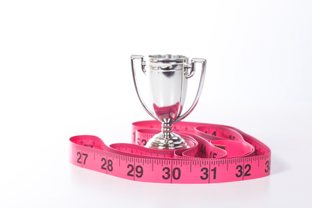 Loosing weight or fitness success concept with small silver champion sports cup and red or pink measuring tape on white surface, viewed from the front in detail