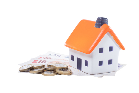 Household expenses or rent cost concept, close-up toy house with orange roof and pile of coins over GBP banknotes isolated on white background with copy space
