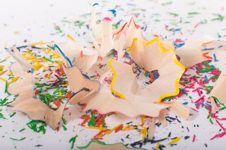 Shavings of sharpened color pencils close-up on white surface, viewed from high angle