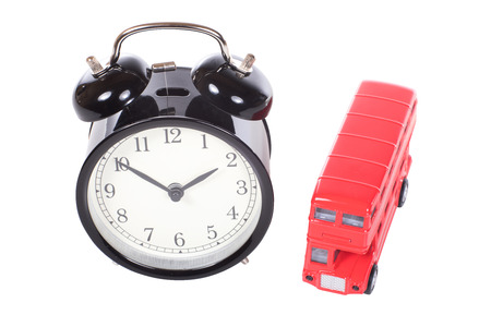 Red London double-decker bus with a retro alarm clock isolated on white viewed high angle in a time and transport concept