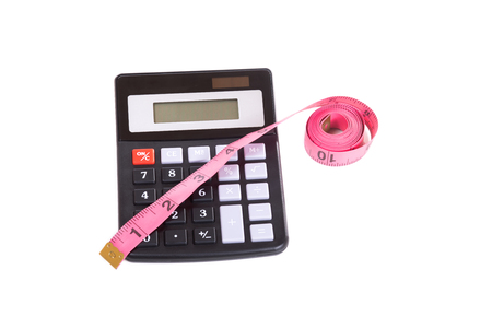 centimetres: Roll of red measuring tape marked in inches and simple calculator viewed from above, isolated on white background with copy space