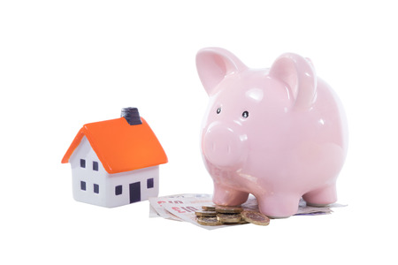 uk money: Little pink piggy bank with a pile of UK money and a model house isolated on white in a concept of saving, deposit, mortgage and purchase of property