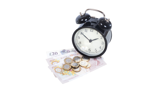 UK pound bills and coins with an alarm clock isolated on white viewed high angle in a financial concept with copy space