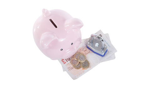 Little piggy bank and door lock over some GBP cash money viewed from above isolated on white background with copy space, as a concept of saving for house expenses or rent