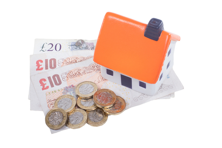 Toy house with orange roof and cash money with coins and GBP banknotes viewed from above, isolated on white background. Household expenses or property rent concept