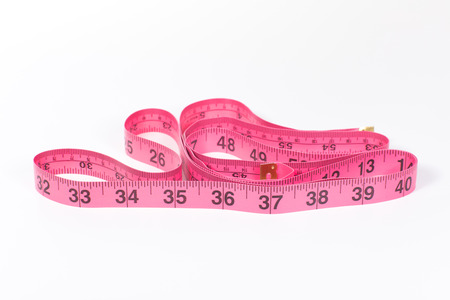 Pink measuring tape unrolled, with 32 to 40 inches in foreground, isolated on white background with copy space
