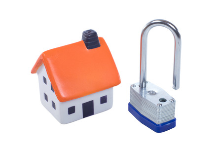 Small toy model of a house with an open steel padlock in a safety and security concept isolated on white Stock Photo