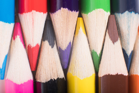 Colored pencils background concept in close-up full frame view, with sharpened tips in opposite to each other