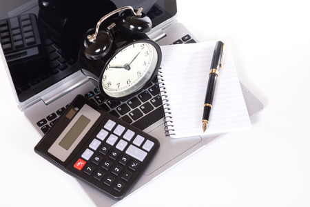 Office objects on laptop keyboard - simple black calculator, blank notebook with fountain pen and classic alarm clock. Viewed from above and isolated on white background