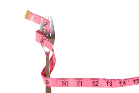 Fork wrapped with a measuring tape through the tines in a concept of loosing weight and dieting isolated on white forming a border