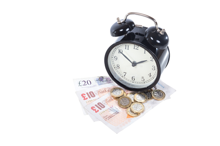 Concept of time management and productivity in business with a retro alarm clock on a pile of British banknotes and coins isolated on white