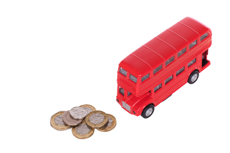 Red double-decker bus with a pile of loose sterling change in a concept of the costs of public transport in Britain isolated on white Фото со стока