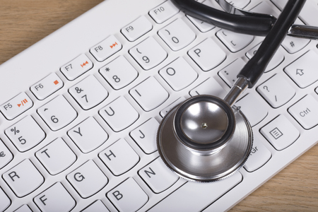 information analysis: Stethoscope lying on a computer keyboard in a concept of troubleshooting and repair or of online medical assistance