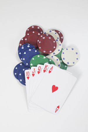 Winning poker hand of playing cards with a straight royal flush resting on a pile of casino chips in a concept of striking it lucky in gambling