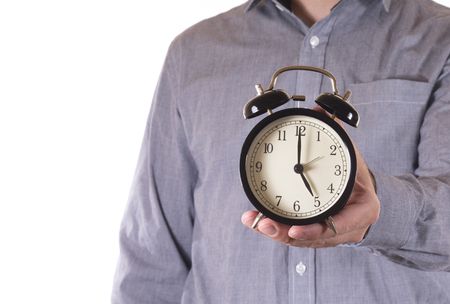 Man holding out a retro alarm clock with the time set to five oclock in a concept of home time from work or business in a close up view Stock Photo