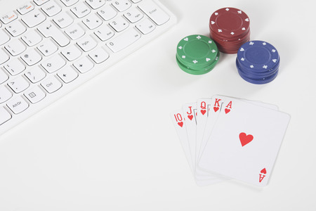 White plastic keyboard next to red green and blue colored poker chips and red and white playing cards Stock Photo