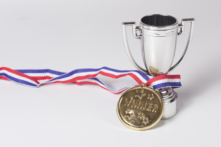 Gold medal winner on a ribbon entwined around a silver trophy to be awarded to the champion in a sporting event with copy space