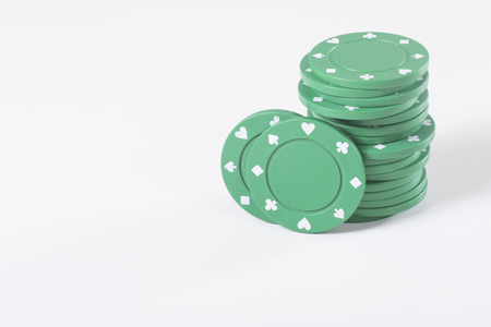 Stack of green casino chips for gambling with two propped upright over a white background with copy space