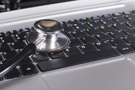 Close up of a stethoscope disc on a laptop in a concept of online medicine or troubleshooting the computer for problems and repair
