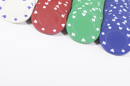 Angled close up on colorful poker chips over white background with copy space below