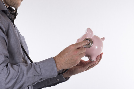 Side view of unidentifiable male doctor examining a piggy bank with stethoscope over white background