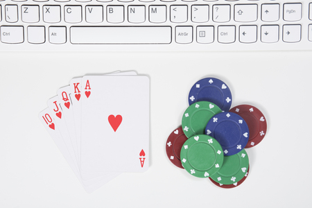 Top down view on winning cards and poker chips below computer keyboard for concept about computer gambling addiction Stock Photo