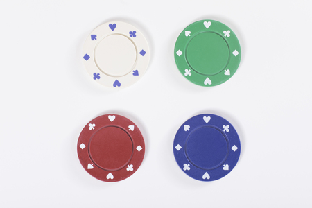 Four casino gambling chips isolated on white in red, green, blue and white for the different denominations issued in a casino