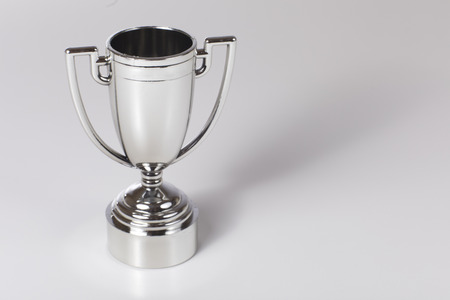 Silver trophy for the winner of a competition over a light grey background with copy space Stock Photo