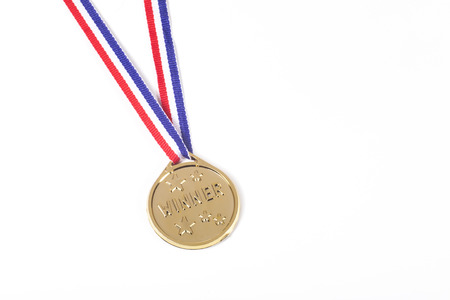 Winners gold medal on a ribbon isolated on white awarded to the first place in a sporting event or competition with copy space
