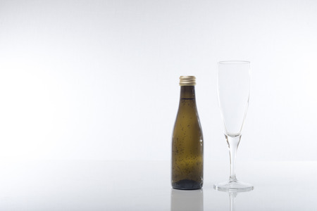 unlabelled: A chilled champagne glass wine bottle with condensed water droplets next to a tall empty wine glass isolated on a white background with copy space.