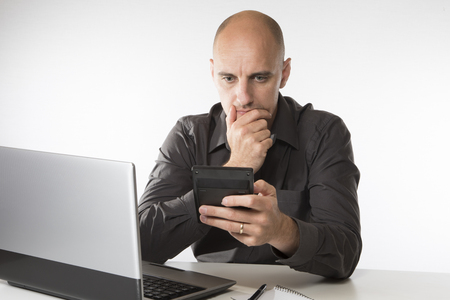 Worried man staring at a handheld calculator as he sits at his desk working on a laptop computer