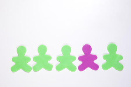 One different purple plastic man in a row of four green forming a lower border with copy space above isolated on white in a conceptual image