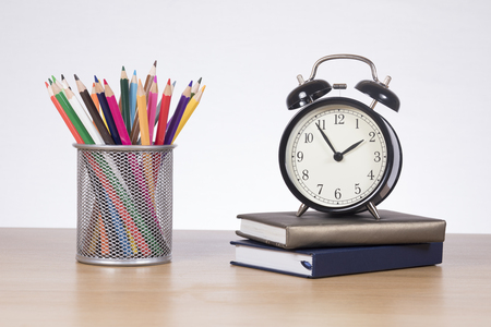 School classes and education concept with a collection of brightly colored pencil crayons in a basket alongside an alarm clock and books on a wooden table